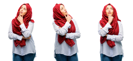 Arab woman wearing hijab thinking and looking up expressing doubt and wonder isolated over white background