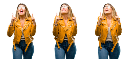 Beautiful young woman happy and surprised cheering expressing wow gesture pointing up over white background