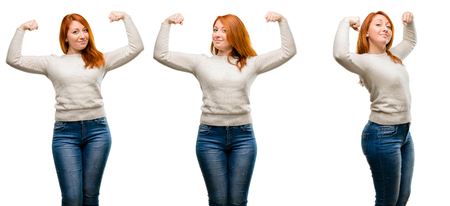 Young Beautiful redhead woman showing biceps expressing strength and gym concept, healthy life its good