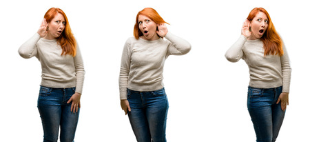 Young Beautiful redhead woman holding hand near ear trying to listen to interesting news expressing communication concept and gossip Stockfoto