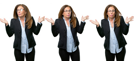 Middle age business woman doubt expression, confuse and wonder concept, uncertain future shrugging shoulders over white background