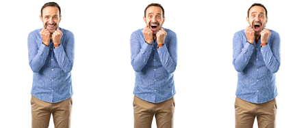 Middle age handsome man happy and surprised cheering expressing wow gesture over white background