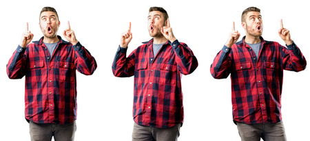 Young man happy and surprised cheering expressing wow gesture pointing up isolated over white background, collage composition