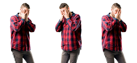 Young man smiling having shy look peeking through her fingers, covering face with hands looking confusedly broadly isolated over white background, collage composition Stock Photo