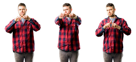 Young man annoyed with bad attitude making stop sign with hand, saying no, expressing security, defense or restriction, maybe pushing isolated over white background, collage composition
