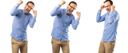 Middle age handsome man happy and excited celebrating victory expressing big success, power, energy and positive emotions. Celebrates new job joyful over white background