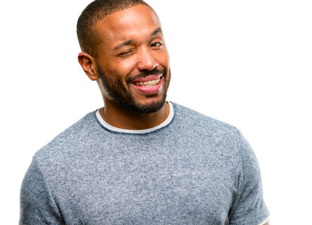 African american man with beard blinking eyes with happy gesture isolated over white background