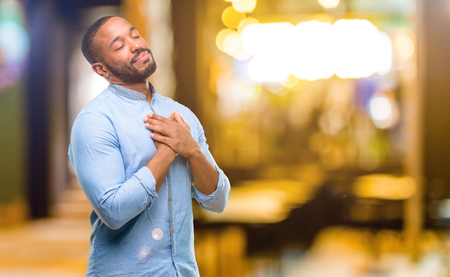 African american man with beard with hands in heart, expressing love and health concept at night