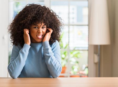 Mujer afroamericana en casa tapándose los oídos con los dedos con expresión molesta por el ruido de la música alta. Concepto de sordos.