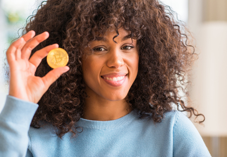 African american woman holding golden bitcoin cryptocurrency at home with a happy face standing and smiling with a confident smile showing teeth Foto de archivo