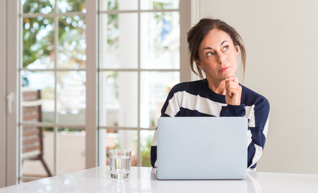 Middle aged woman using laptop at home serious face thinking about question, very confused idea
