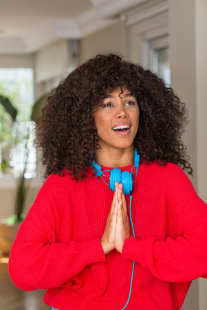 African american woman wearing headphones begging and praying with hands together with hope expression on face very emotional and worried. Asking for forgiveness. Religion concept.