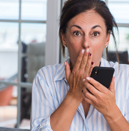 Middle aged woman using smartphone cover mouth with hand shocked with shame for mistake, expression of fear, scared in silence, secret concept