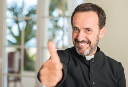 Christian priest man happy with big smile doing ok sign, thumb up with fingers, excellent sign Banque d'images