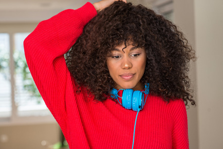 African american woman wearing headphones confuse and wonder about question. Uncertain with doubt, thinking with hand on head. Pensive concept. Stock Photo