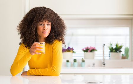 African american woman drinking orange juice in a glass with a confident expression on smart face thinking serious