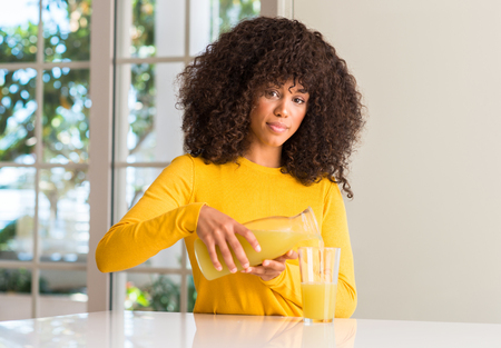 African american woman drinking healthy fruit juice at home with a confident expression on smart face thinking serious
