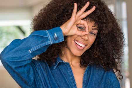African american woman with happy face smiling doing ok sign with hand on eye looking through fingers