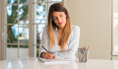 Beautiful young woman thinking while studying and reading at home