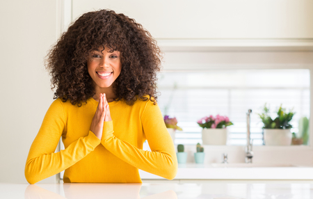 African american woman wearing yellow sweater at kitchen praying with hands together asking for forgiveness smiling confident.