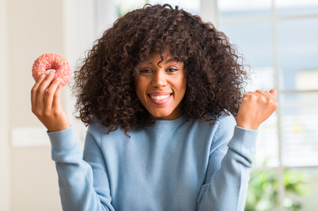 African american woman holding donut at home screaming proud and celebrating victory and success very excited, cheering emotion Stock Photo