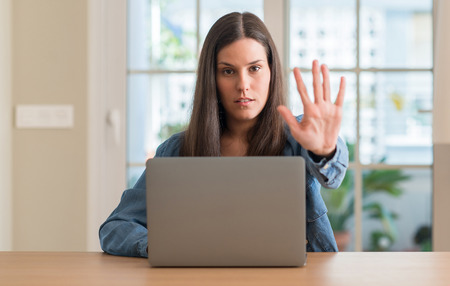 Young woman using laptop at home with open hand doing stop sign with serious and confident expression, defense gesture 스톡 콘텐츠