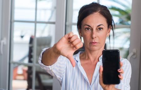 Donna di mezza età che utilizza smartphone con la faccia arrabbiata, segno negativo che mostra antipatia con i pollici in giù, concetto di rifiuto Archivio Fotografico - 103864567