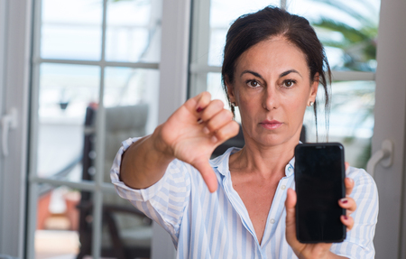 Middle aged woman using smartphone with angry face, negative sign showing dislike with thumbs down, rejection concept Archivio Fotografico - 103864567