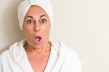 Beautiful middle age woman, wet hair wearing a towel scared in shock with a surprise face, afraid and excited with fear expression
