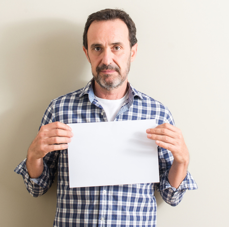 Senior man holding blank paper sheet with a confident expression on smart face thinking serious