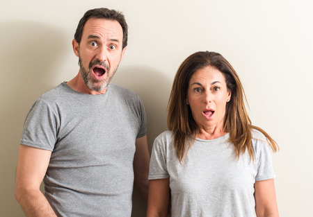 Middle age couple, woman and man scared in shock with a surprise face, afraid and excited with fear expression Foto de archivo