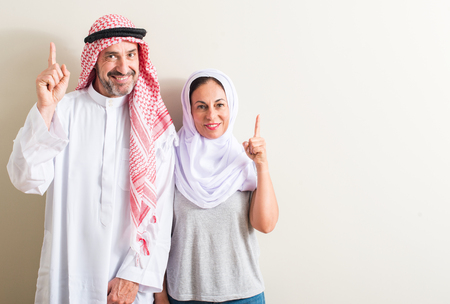 Middle age arabic couple, woman and man surprised with an idea or question pointing finger with happy face, number one