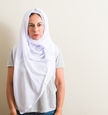 Middle age arabian woman wearing white hijab with a confident expression on smart face thinking serious