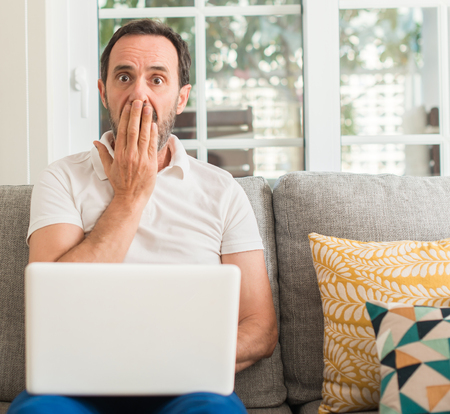 Middle age man using laptop at sofa cover mouth with hand shocked with shame for mistake, expression of fear, scared in silence, secret concept