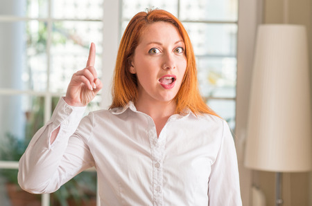 Redhead woman wearing white shirt at home surprised with an idea or question pointing finger with happy face, number one Stock Photo