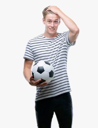 Young handsome blond man holding soccer ball stressed with hand on head, shocked with shame and surprise face, angry and frustrated. Fear and upset for mistake.
