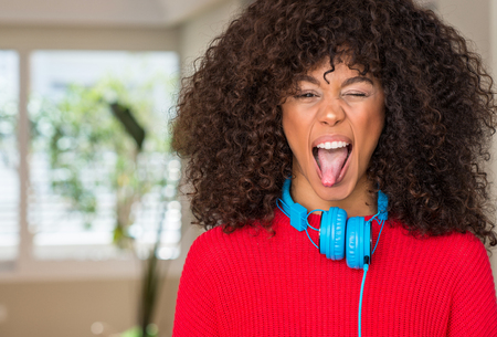 African american woman wearing headphones sticking tongue out happy with funny expression. Emotion concept.