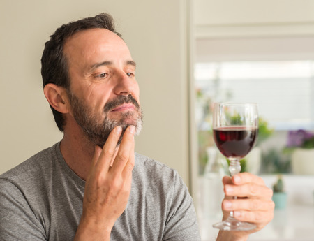 Middle age man drinking a glass of wine serious face thinking about question, very confused idea Stock Photo