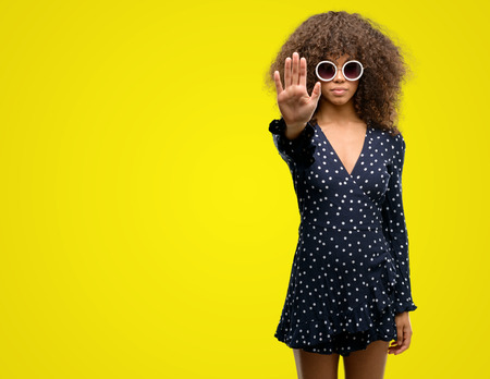 African american woman with sunglasses and summer dress with open hand doing stop sign with serious and confident expression, defense gesture