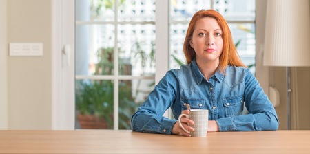 Redhead woman holding a cup of coffee with a confident expression on smart face thinking serious