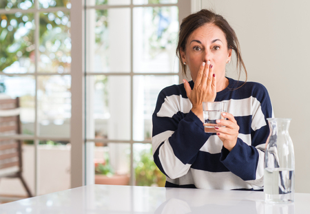 Middle aged woman drinking a glass of water cover mouth with hand shocked with shame for mistake, expression of fear, scared in silence, secret concept Stock Photo