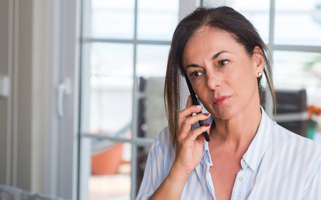 Middle aged woman using smartphone with a confident expression on smart face thinking serious Фото со стока
