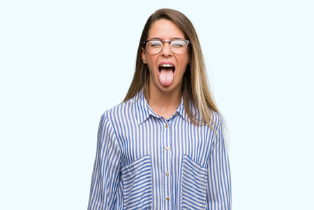 Beautiful young woman wearing elegant shirt and glasses sticking tongue out happy with funny expression. Emotion concept.
