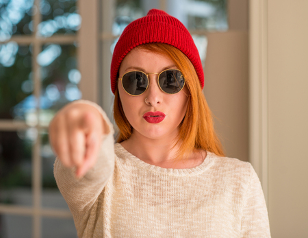 Stylish redhead woman wearing wool cap and sunglasses pointing with finger to the camera and to you, hand sign, positive and confident gesture from the front