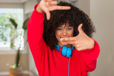 African american woman wearing headphones smiling making frame with hands and fingers with happy face. Creativity and photography concept.