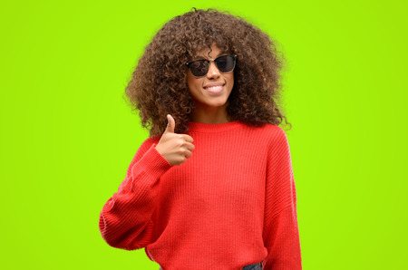 African american woman wearing sunglasses smiling broadly showing thumbs up gesture to camera, expression of like and approval