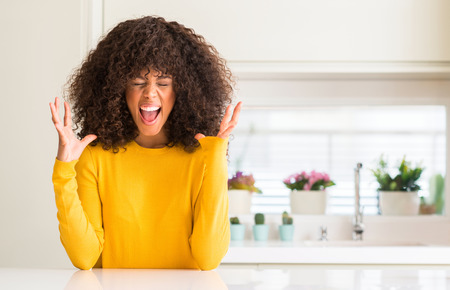 African american woman wearing yellow sweater at kitchen celebrating mad and crazy for success with arms raised and closed eyes screaming excited. Winner concept Stock Photo