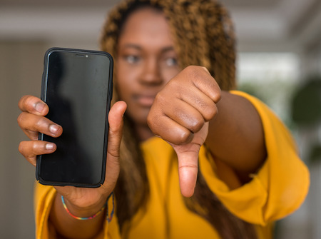 African american woman using smartphone with angry face, negative sign showing dislike with thumbs down, rejection concept