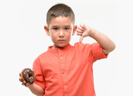 Dark haired little child eating doughnut with angry face, negative sign showing dislike with thumbs down, rejection concept Stock Photo