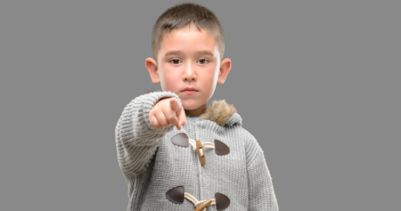 Dark haired little child wearing a coat pointing with finger to the camera and to you, hand sign, positive and confident gesture from the front